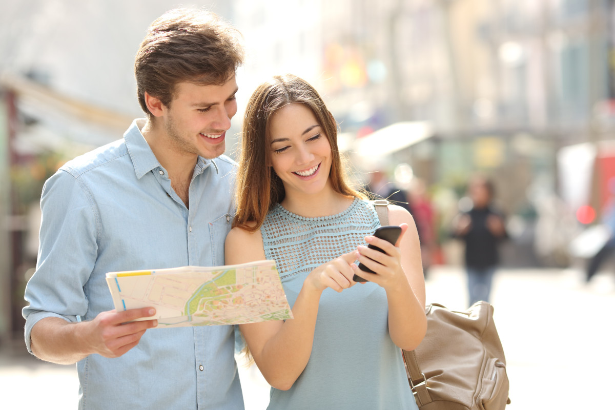 Couple of tourists consulting a city guide and smartphone gps in the street searching locations