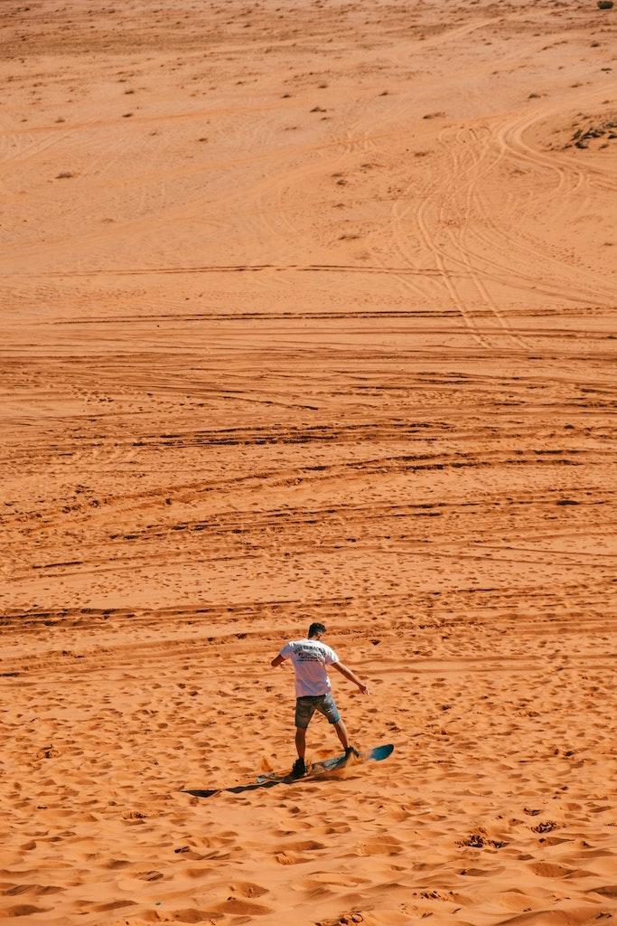 Man sandboarding down a dune.