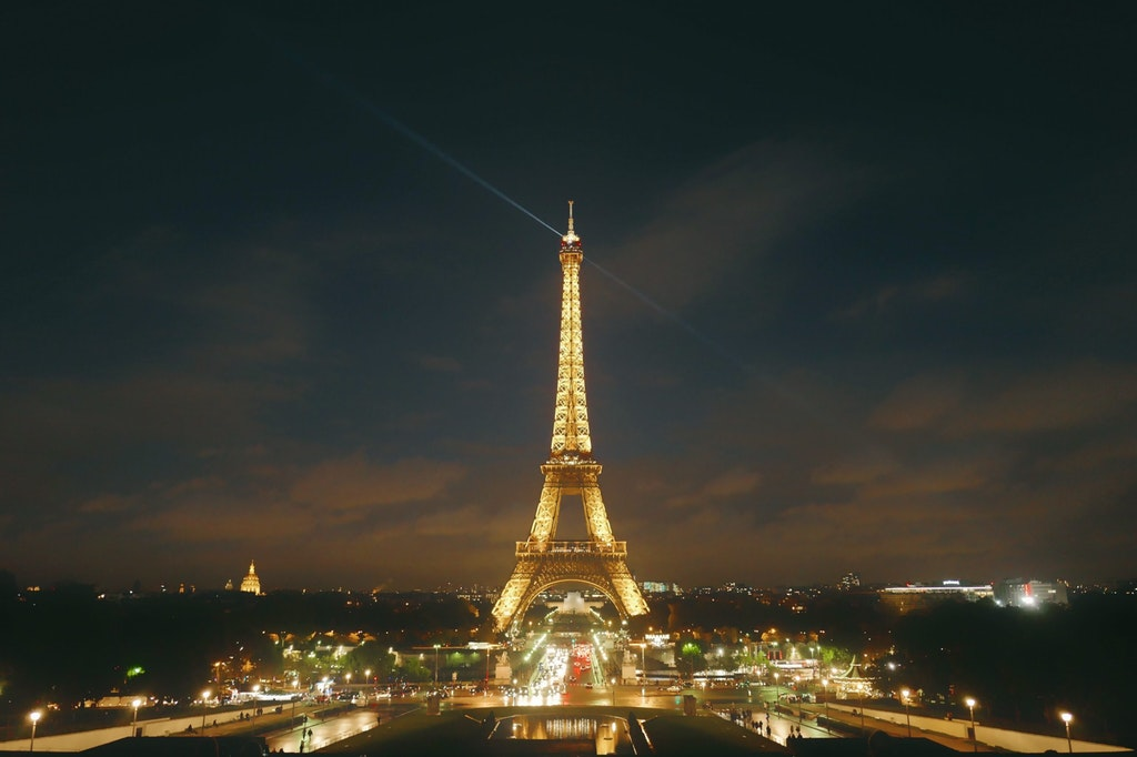 Eiffel tower in the night time decorated with flashing lights of Paris