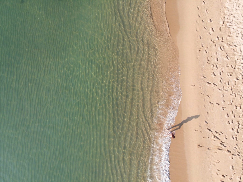 A aerial view of a woman enjoying the waves of Bogatell Beach, one of the best beaches in Barcelona