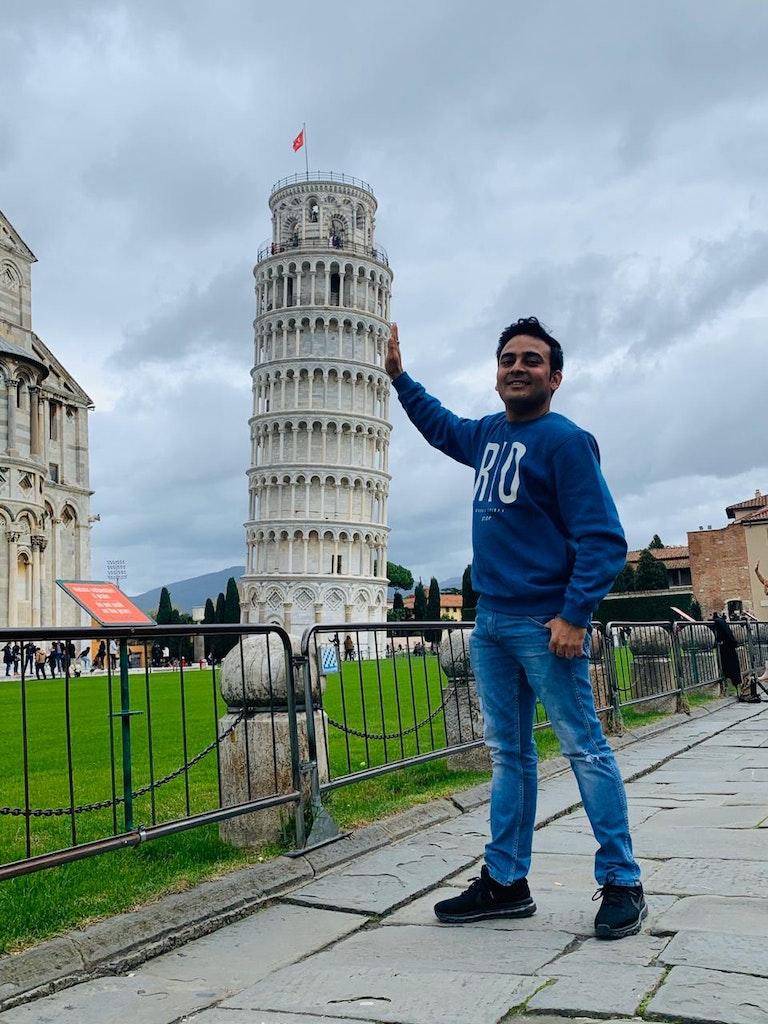 A man posing in front of Pisa