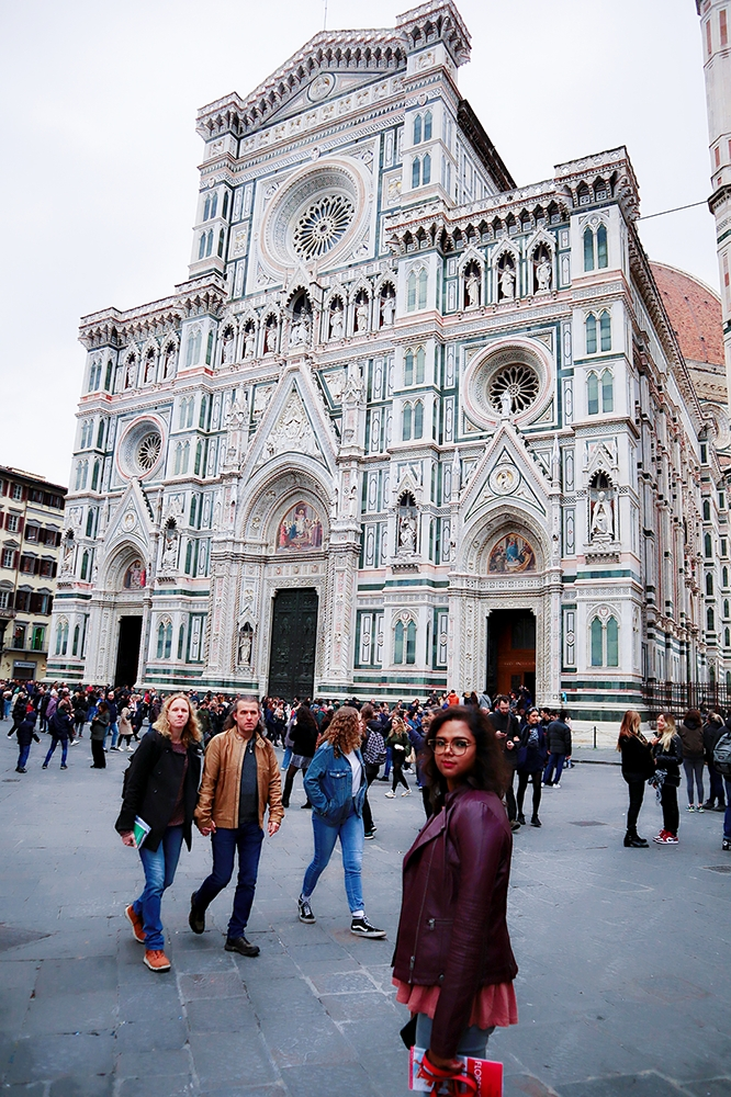 A girl posing in front of the famous attraction on their honeymoon to Italy