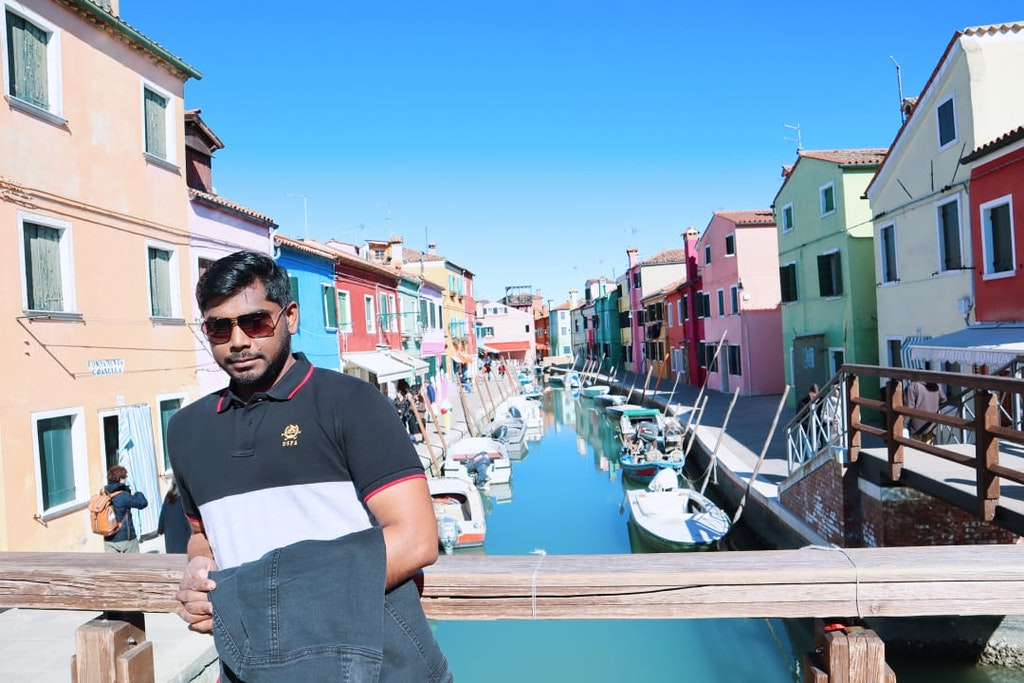 A picture of guy standing in the island of Burano in Italy