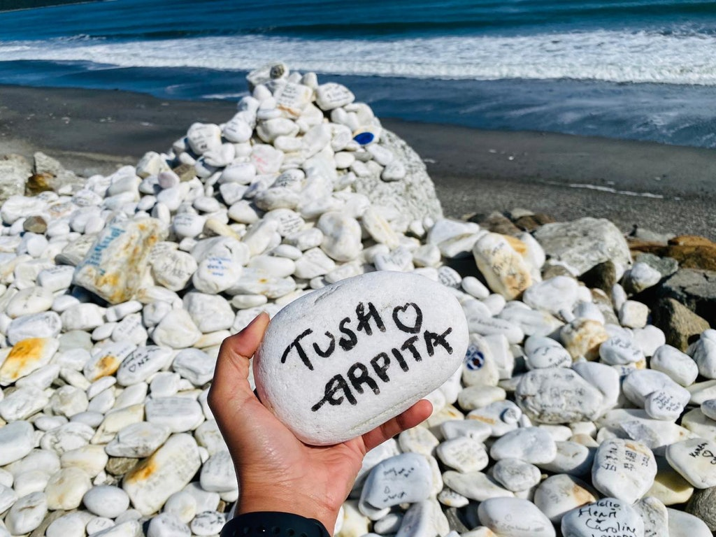 A couple names beautifully written in a white stone on the beach