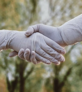 A couple holding hand covered in gloves.
