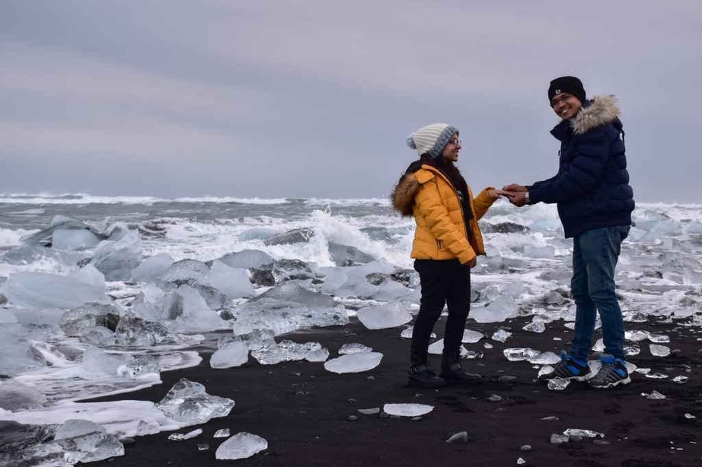 A beautifully captured picture of a couple proposal on the diamond beach in Iceland