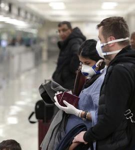 A picture of people waiting at the airport with masks covering their faces