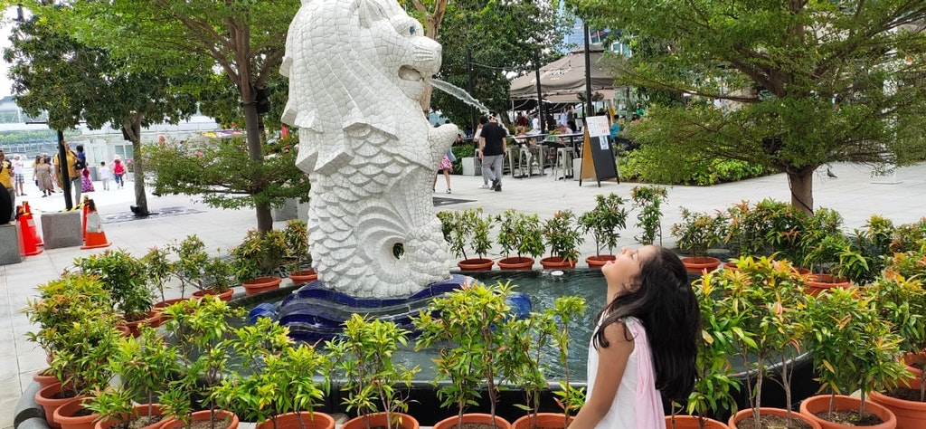 My daughter posing with the lion during our family vacation to Singapore