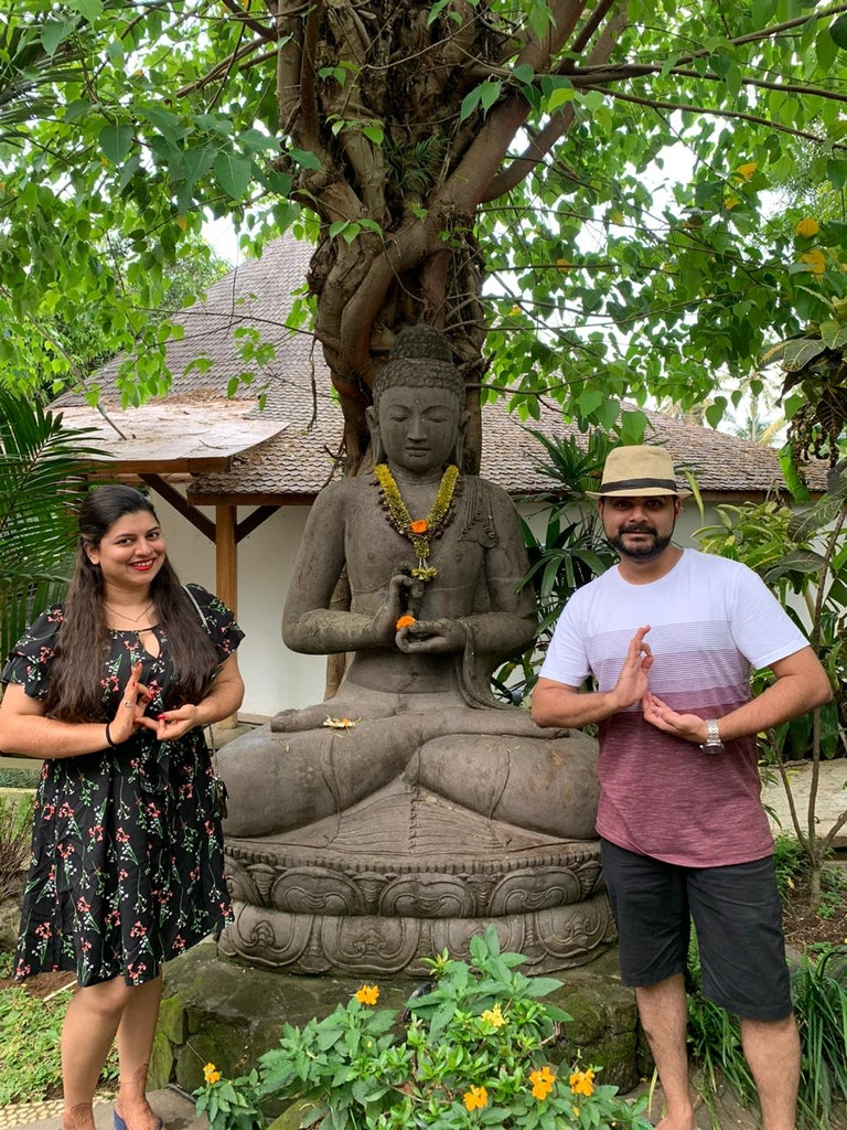 A couple trying to copy the pose of a statue in Bali
