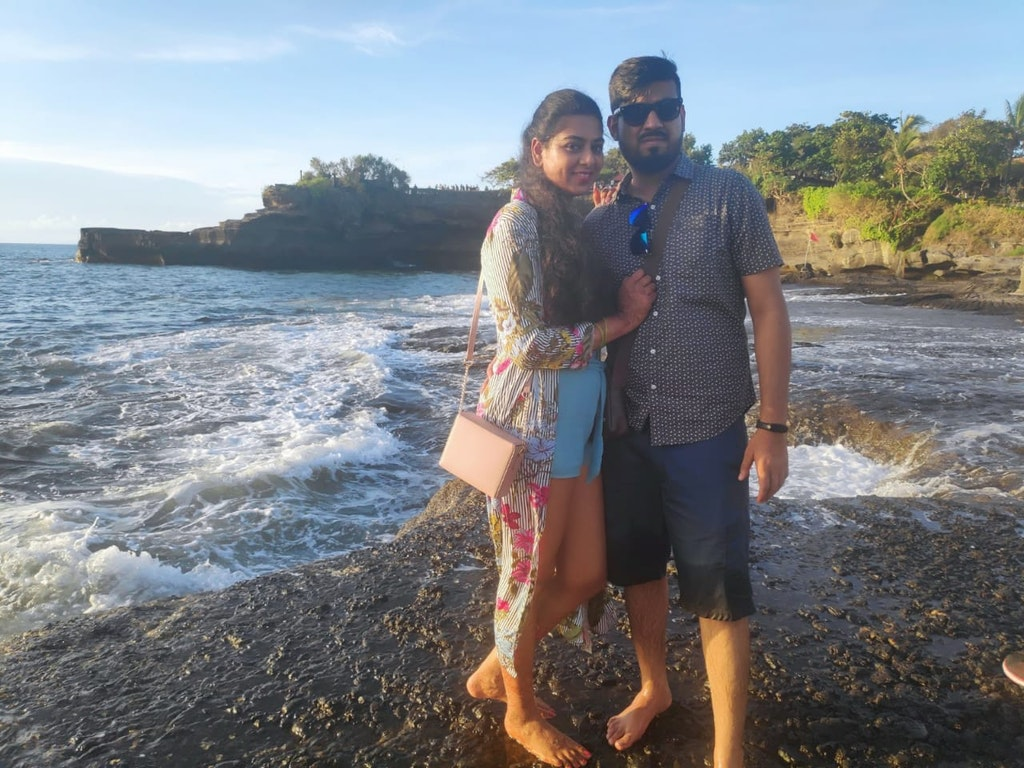 A couple posing with beach as the background