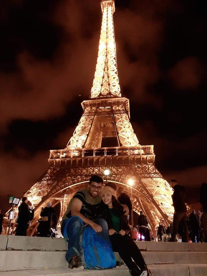 A beautiful picture of a couple at Eiffel tower in lights on their honeymoon vacation to Europe