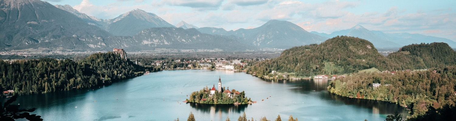 A wide shot of lake bled and Bled castle on the cliff.