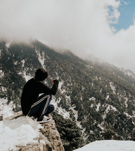 A guy sitting on the rock mountain