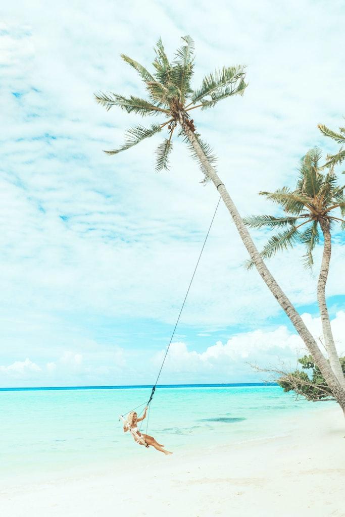 a girl swinging on the beach.