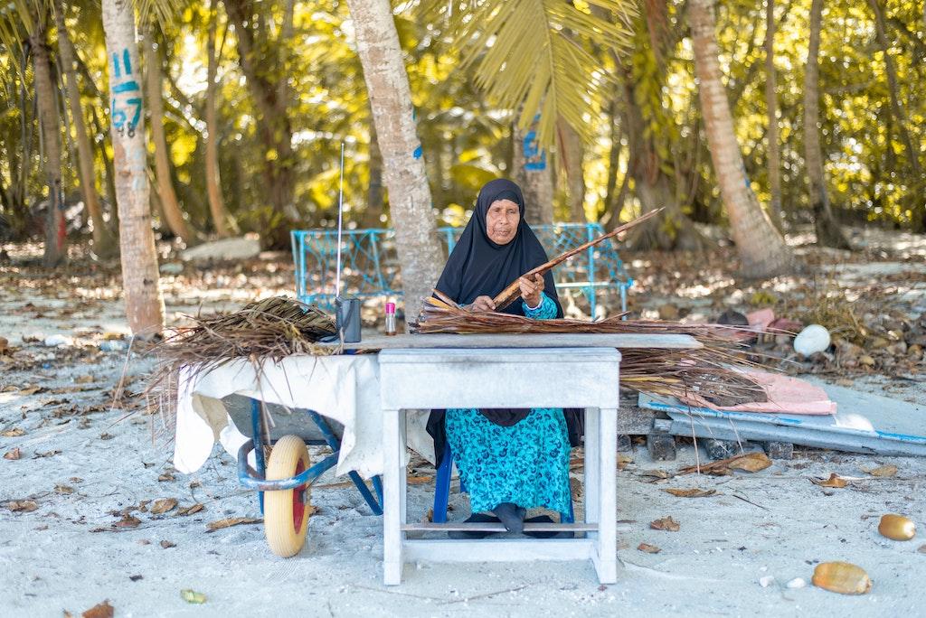 Maldives woman weaving handicrafts