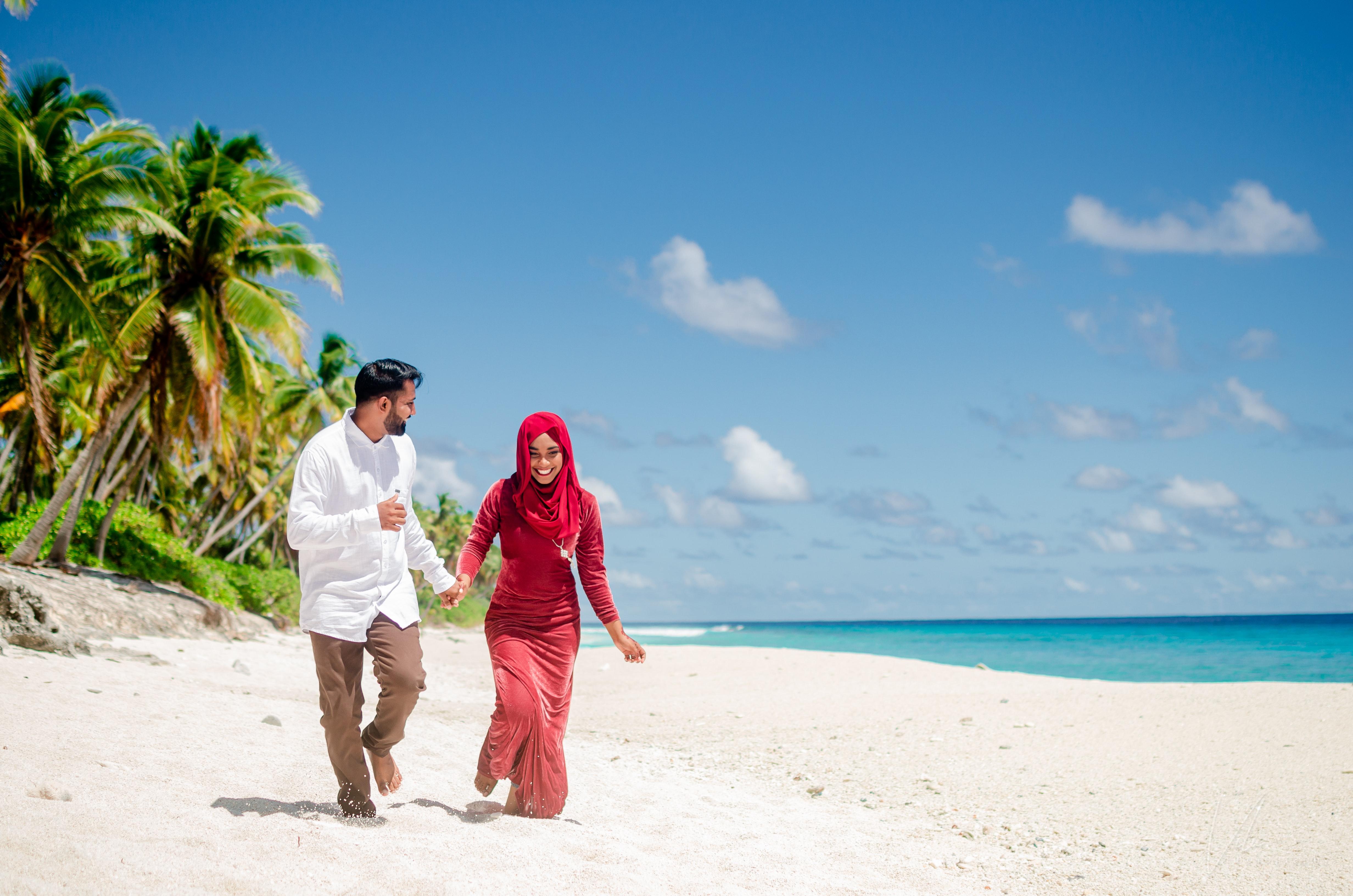 A Honeymoon couple walking along the shores of Maldives beaches